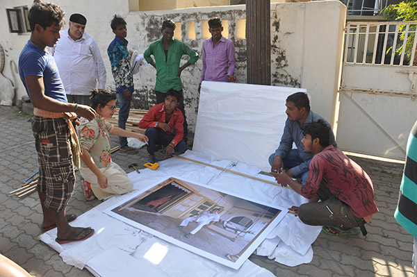 Preparing photograph for display on road near Iranshah